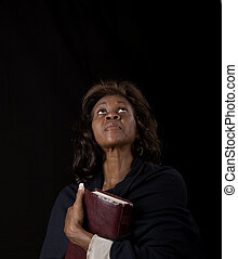 Woman Holding Bible Looking Up - A black woman clutching a...