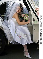 Bride exiting wedding car limousine - Smiling bride with...