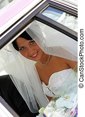 Bride smiling through window of wedding car limousine -...