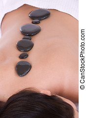 Hot stone massage - Woman lying on the massage table with...
