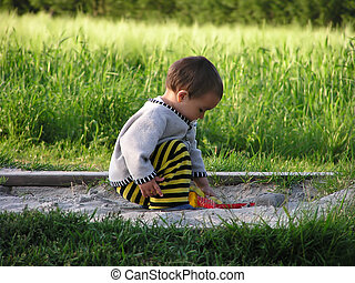 young child in sand pit - Young boy concentrated playing in...