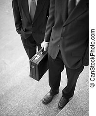 businessmen - two businessmen standing on steps with hands...