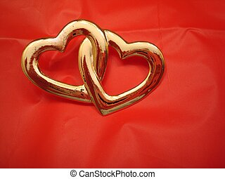 Two Entwined Hearts - Two enteined hearts on red.