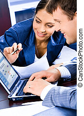 Teamwork - Business woman pointing at laptop and explaining...