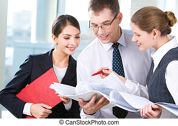 Business meeting - Three business people are discussing a...
