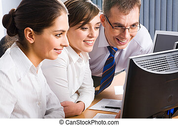 Business team - Team of three business people looking at the...