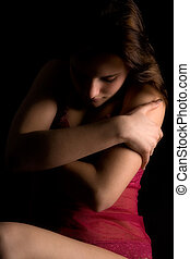 Low key lingerie embracing - Studio portrait of a woman in...