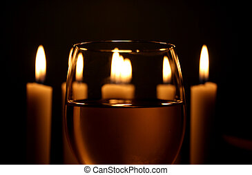 Wine glass with white candlelights in the background