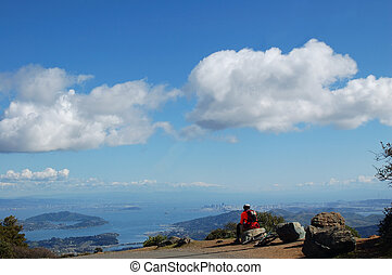 Bay Views - Mountain Biker rests near the East Summit of Mt....