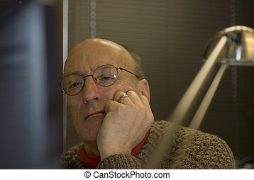 man looking at computer screen in office