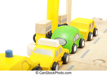 At gas station - Cue of toy wooden coloured cars to gas...