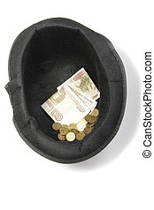 Money in hat - Paper money and coins in a black hat over...