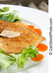 Seasoned flaky white fish on a salad