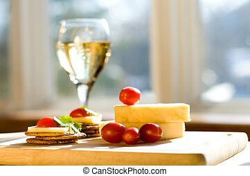 Wine and cheese - cheese and crackers on a cutting board