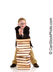 Young boy on books - Young boy, prodigy holding magnifying...
