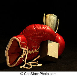 red boxing glove holding a shining cup - dark background and...