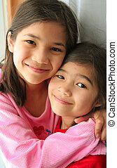 Two sisters smiling - Two girls hugging and smiling. Part...