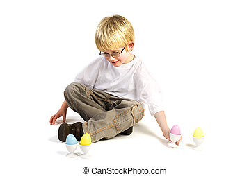 play with eastereggs - a little blond boy is playing with...
