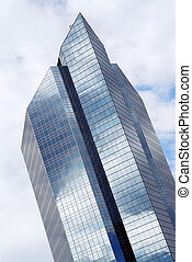Corporate building with glass walls reflecting clouds