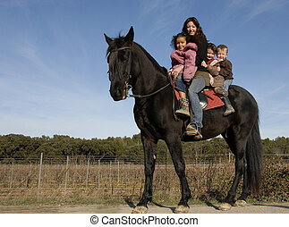 riding family - children and mother and a black stallion on...