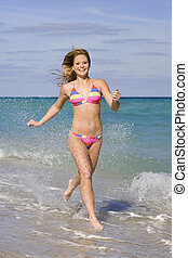 Beach - Beautiful Caucasian female teenage running through...