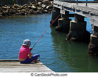 girl fishing - a little girl sits on the dock and goes...