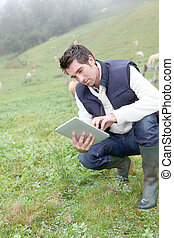 Breeder using electronic tablet in field
