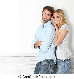 Young couple standing on white wall