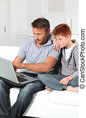 Man and child at home with laptop computer
