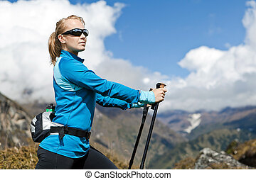 Woman nordic walking and exercising in mountains