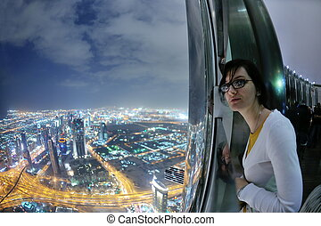 beautiful woman portrait with big city at night in background
