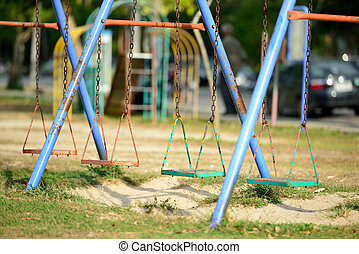 The unoccupied swing is on the playground.