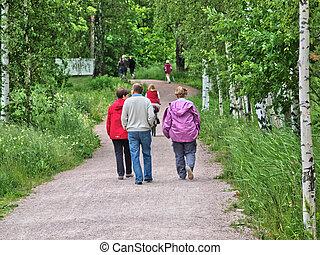 Elderly people having a walking on a gravel road