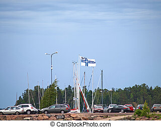 Finnish flag waving strong in the wind at harbor