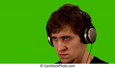 man on a green background listens to music