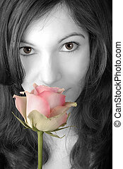 Smelling a rose - Beautiful young woman smelling a pink rose...