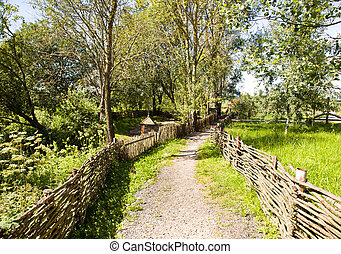 foot path - made of tree rods a fence. traditional for...