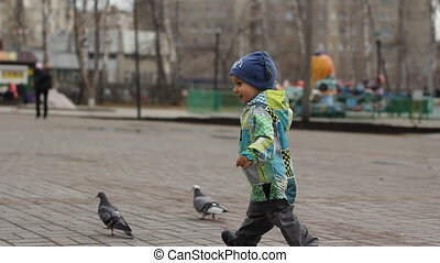 Baby laughs and runs to pigeons in the park