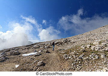 hiker on rocky mountain - woman walks on alpine pathway -...