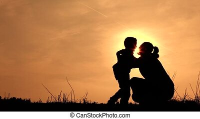 Mum and son hugging silhouette - a boy runs towards his mum,...