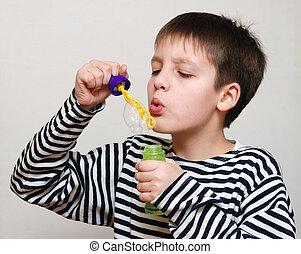 Boy blows soap bubbles