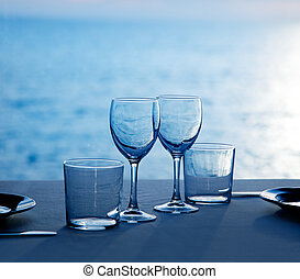 Glass dish cups and glasses on blue sea background