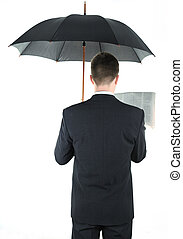 Businessman with an umbrella reading a newspaper