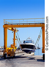 crane travelift lifting a boat on blue sky day in balearic...
