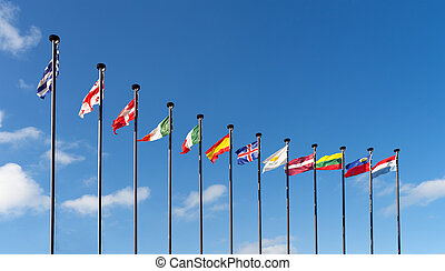 Flags of different countries are developing on the flagpoles