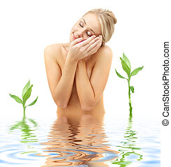 happy blonde with flower petals and green plants in spa -...