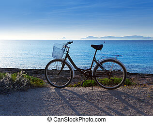 Bicycle in formentera beach with Ibiza sunset