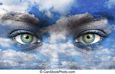 Blue human eyes with sky pattern