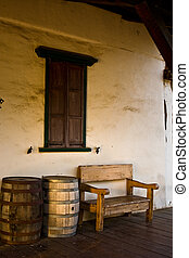 Bench and Barrels - A wooden bench, window and barrels in...