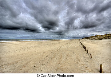 Lonely Beach - Lonely beach with dark clouds on the Dutch...
